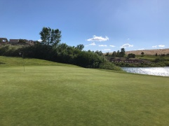 "Side view of 13th green with ""The Hills"" inscribed on the other side of the pond."