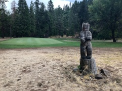 One of several wood carvings around the course in front of the par-3 4th green.