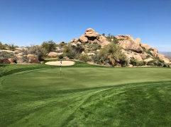Closer view of 15th green with cool boulder formation behind.