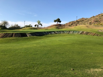 Closer view of 15th green and wall in front.